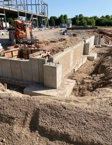 Foundation walls and footings for Area C are complete and have now moved into Area D. The footings you see here will make up the entrance from the playground.