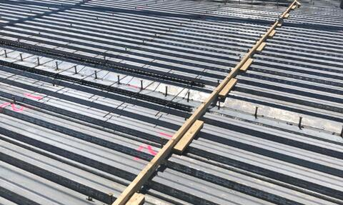 Rebar reinforcement and pour stops are being laid out on the second floor in preparation for the concrete slab. The slab is being poured on Monday.
