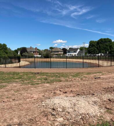 After being seeded and fenced off, the new retention pond is ready to go.