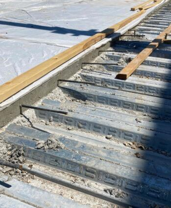 The rebar dowels are placed on slab edges to tie the two slabs together and provide strength at the joints.