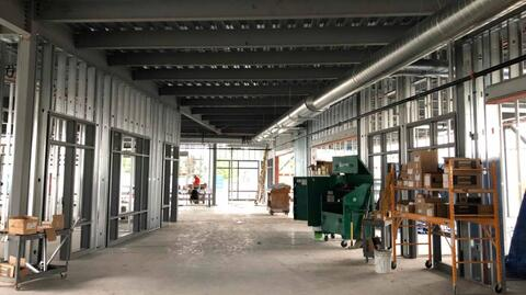 The steel studs, door frames, and window frames are installed through the main classroom corridors.