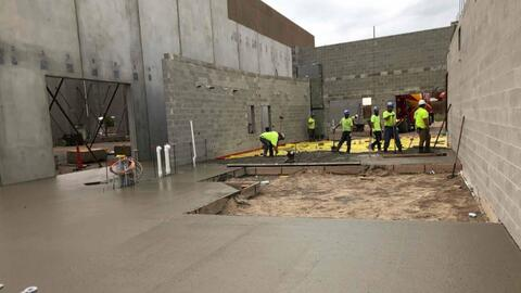 The team is pictured here working on the concrete floor in the kitchen.  The area that is blocked off is the location of the walk-in cooler and freezer.