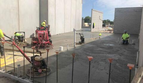 The concrete finishers are smoothing out some freshly poured concrete.  The areas they are working in right now are the bathrooms and corridor just south of the gym.