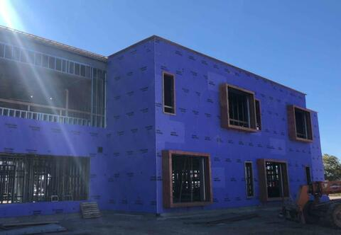 The exterior sheathing on the north side of the school has started.  All the openings wrapped in wood will be the bumped out windows found in every classroom.
