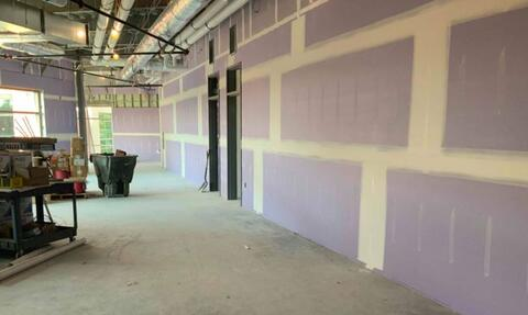 Drywall is being taped and finished in the new classroom addition.
