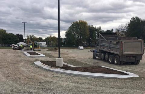 Concrete curbs are being installed throughout the parking lot.