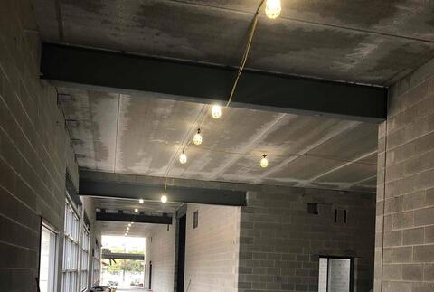 The precast concrete plank has been installed over the corridor of the athletic area.