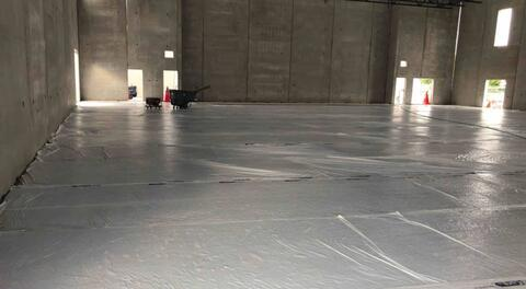 The concrete floor in the gym has been poured and is covered as it cures.
