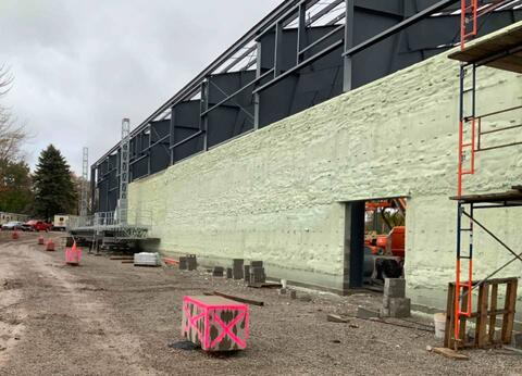 The wall on the west side of the new turf building has received spray foam insulation and is ready for facebrick.