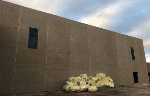 The windows on the east side of the gym are installed and the joints between the precast panels have been caulked and are ready to be washed.