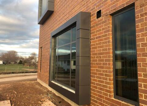 The window bumpouts at the classrooms and being finished with charcoal gray metal panels.