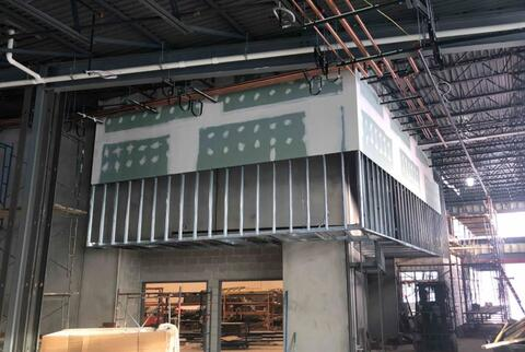 The soffits in the cafeteria are framed with drywall taping and finishing underway.