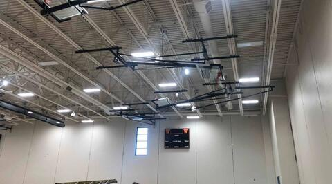 With the gym finally painted, the basketball hoops, scoreboards, and dividing curtain have been installed.