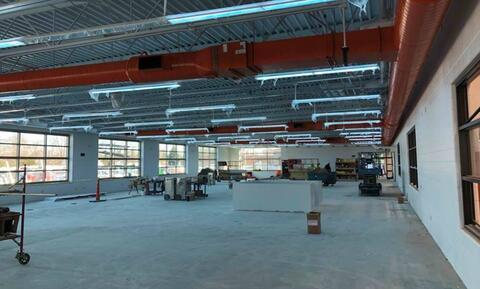 Electricians installing lighting in weight room.