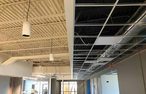 The ceiling grid is complete in the hallway soffit and pendant lights have been installed in the open ceiling areas throughout the second floor.