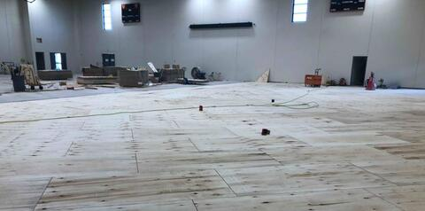 The wood floor is being installed in the gym.  Under the base layer of plywood are small rubber pads that help cushion the floor.