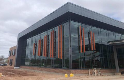 The library curtain wall at the front of the school is nearly complete with the orange sun shades installed.