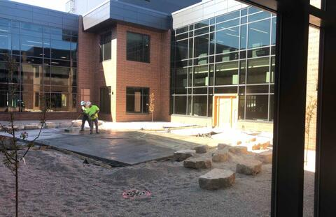 In the courtyard the landscaping is in place and the concrete is being poured.