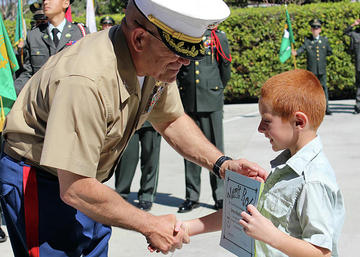 Veteran giving a certificate to a young boy.