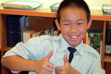 Boy giving a thumbs up sign
