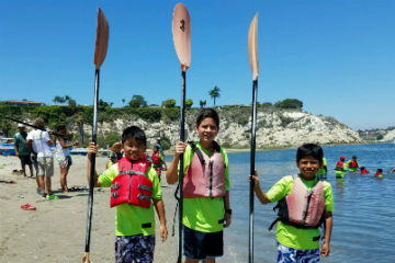 Students holding kayak paddles