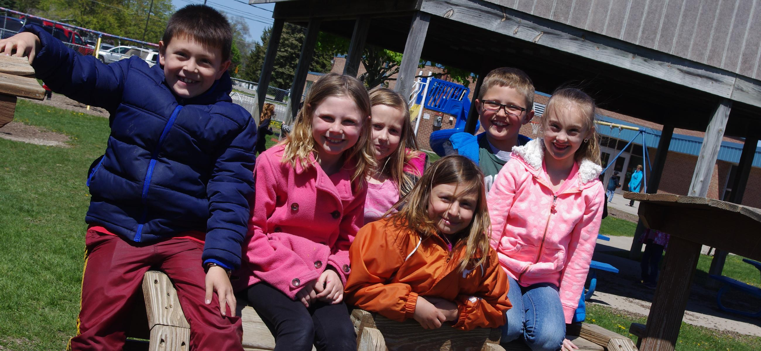 Students outside on the playground, wearing coats and smiling