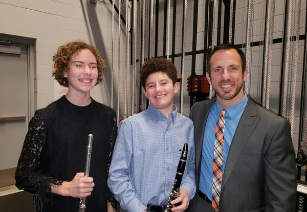 Two MJHS students and the band Director pose for a picture at the District 14 Honors Band Concert