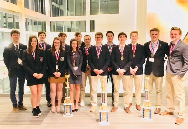 Group of students posing at DECA Competition with trophies