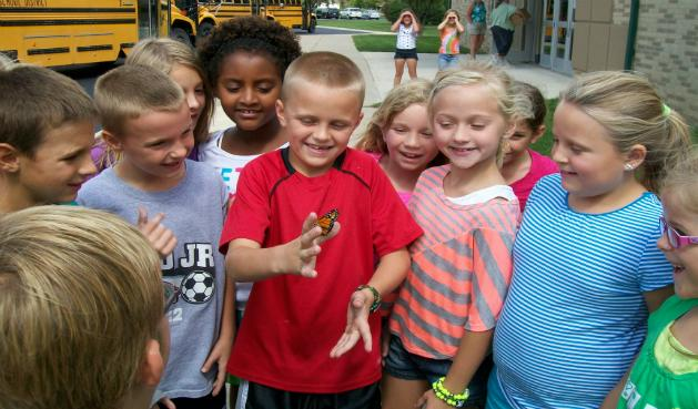 Group of students smiling and looking at a monarch butterfly