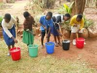 Photo shows Students stir water purification packets into the bucket