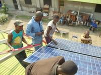 Photo shows Villagers install a solar panel array on a roof-top