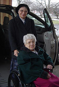 Sister Rose and a woman on a wheel chair picture