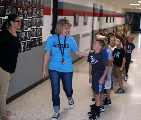 teacher walking her student down the hallway