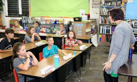 students listening to classroom teacher teach
