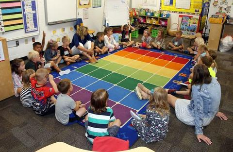 children and teacher sitting around rug in classroom