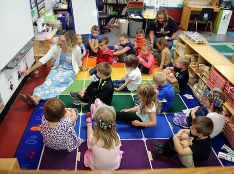 children in classroom listening to teacher teach