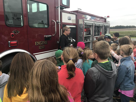 children and firefighter outside by fire truck