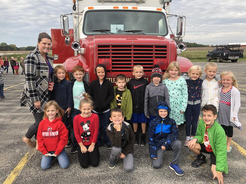 teacher and students outside by fire truck