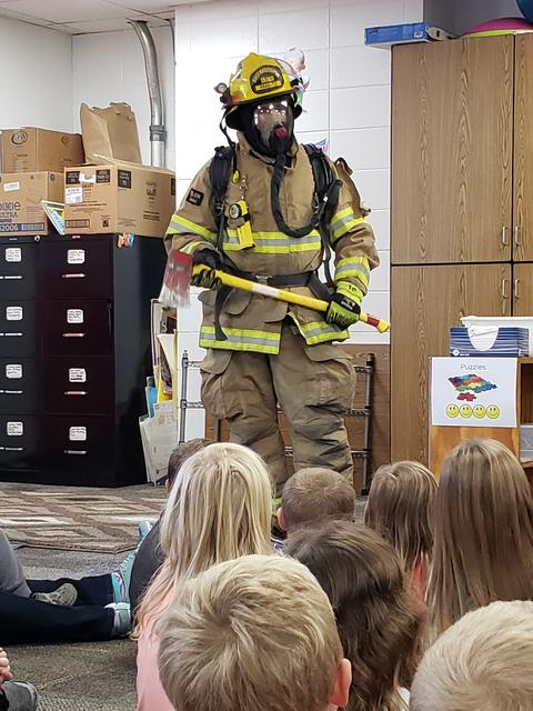 firefighter in classroom presenting to children