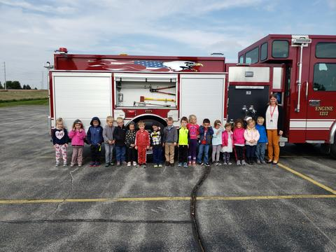 teacher and students outside by firetruck