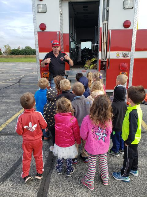 children and firefighter outside by firetruck
