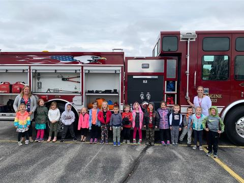 teachers and students outside by fire truck
