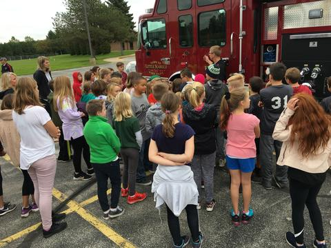 children outside by fire truck