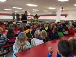 firefighters presenting fire safety to children