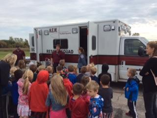 emergency personnel and children outside by rescue vehicle