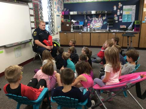 police officer talking to children in classroom