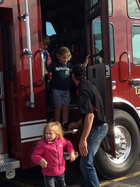 firefighter helping child step out of fire truck