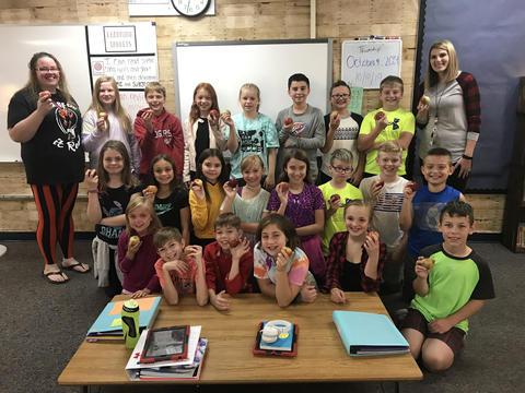 teacher & students holding apples