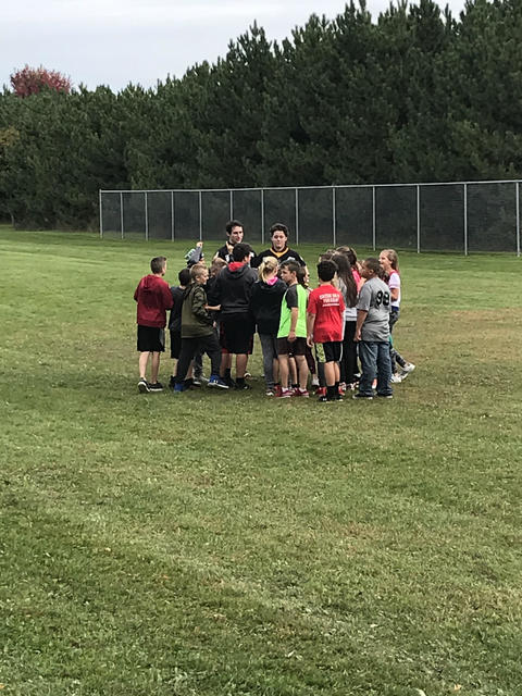 children and Green Bay Gambler players outside in a huddle