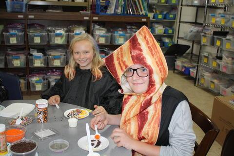 kids in costumes decorating cookies